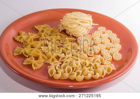 Macaroni Of Different Species On A Brown Round Plate