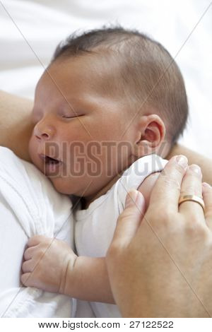 Sleeping newborn baby in mothers arms