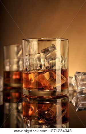 Chilled Whiskey Glasses With Ice Cubes In Brown Tones