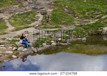 A Woman Wearing Sunglasses And Hiking Attire Sits Contemplatively On The Lakeshore