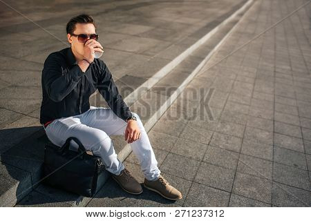 Calm And Peaceful Young Man In Glasses Sit Outside On Steps And Look Forward. He Drinks From Cup. It
