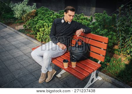 Serious Young Man Sit On Bench Outside And Look At Watches. There Are Two Cups And Black Leather Bag