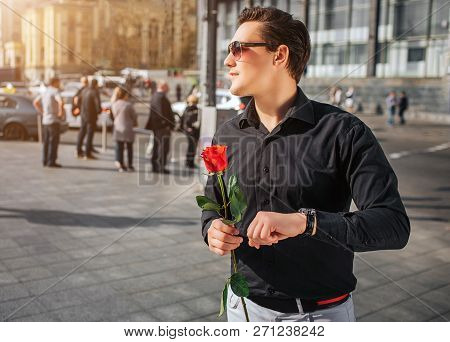 Young Man In Black Shirt Stand Outside And Hold Red Rose In Hands. He Looks Aside Through Sunglasses