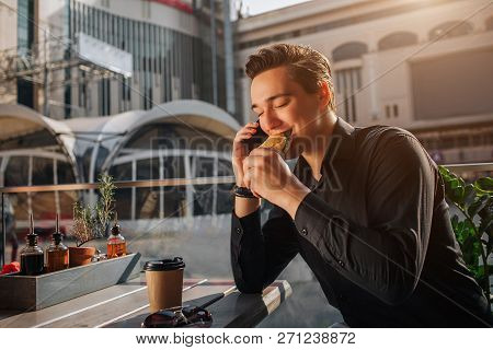Cheerful Young Man Sit At Table Outside And Eat Salty Roll. He Keep Eyes Closed. Guy Talk On Phone.