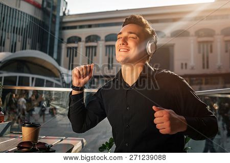Happy Young Man Enjoys Listening To Music. He Dance At Table Outside. Guy Wave With Hands. It Is Sun