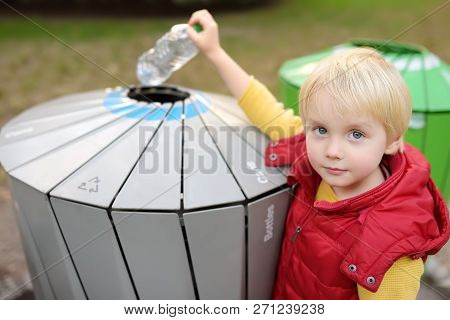 Little Boy Puts A Plastic Bottle In Trash Can For Separate Recycling.ecology, Recycling And Protecti