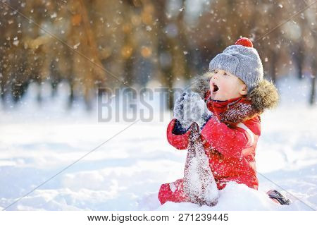 Little Boy In Red Winter Clothes Having Fun With Snow. Active Outdoors Leisure With Children In Wint