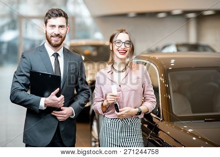 Portrait Of A Handsome Salesperson With Woman Client Standing In The Showroom