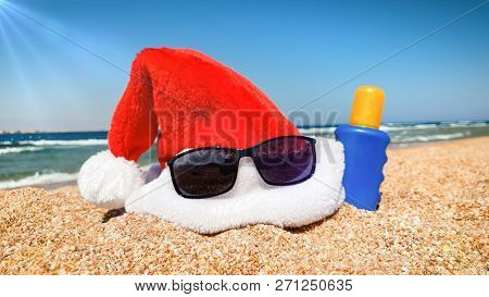 Closeup Photo Of Santas Hat And Sunglasses On The Beach. Concept Of Travel And Tourism On Christmas,