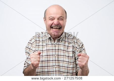 Senior Handsome Man Laughing And Looking At Camera With A Big Grin.