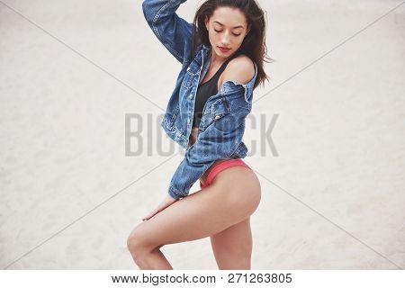 Beautiful Slim Luxury Girl In Bikini And Jeans Jaket On The Sand Beach On A Tropical Island. Sexy Ta