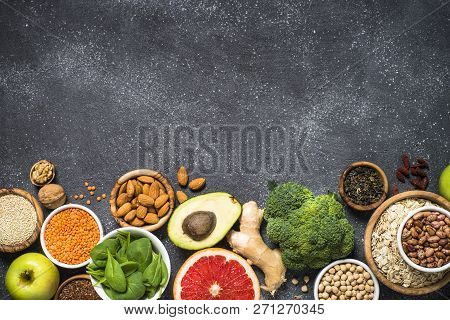 Superfoods On Black Stone Background. Organic Food And Healthy Vegan Food. Legumes, Nuts, Seeds, Fru