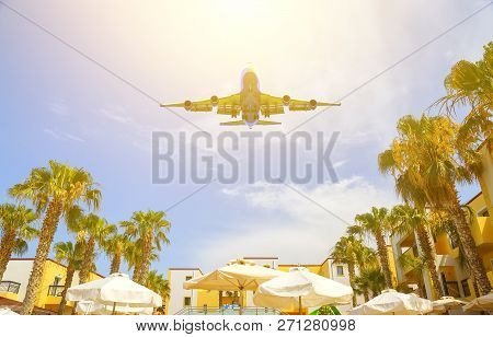 Large Jumbo Jet Between Palm Trees Above The Resorts Rooftops In The Sun. Bright Open Concept Beach