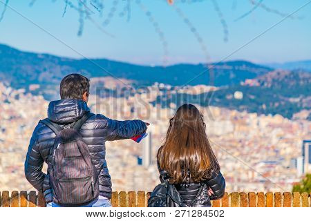 Young couple with winter clothes watching the view of barcelona city from montjuic castle poster