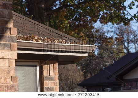 Pile Of Dried Leaves On Rain Gutter Of Residential Home In Texas, America