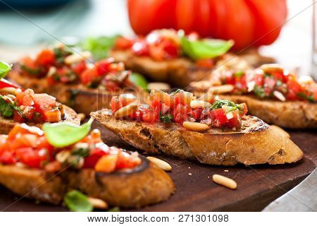 Bruschetta, On Slices Of Toasted Baguette Garnished With Basil.
