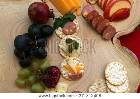 Appetizers on a tree stump cutting board for a Christmas Meal. Appetizers consisting of cheeses, fruits, sausages, crackers and fresh herbs. Wooden Tree Stump Cutting board on a red table cloth.