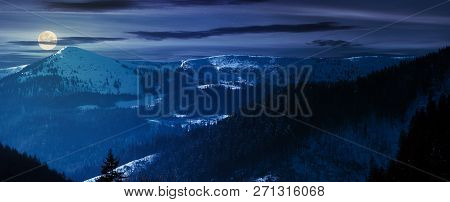 Panorama Of Mountain Ridge And Forested Hills At Night In Full Moon Light. Lovely Winter Scenery