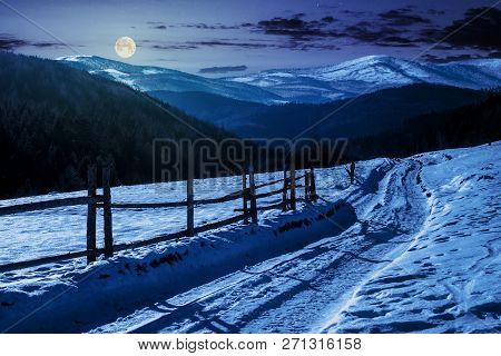 Country Road In To The Winter Mountains At Night In Full Moon Light. Wooden Fence Along The Road. Co