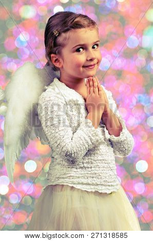 Pretty cute adorable little angel girl. Cute child girl posing with angel wings on glitter shining background..