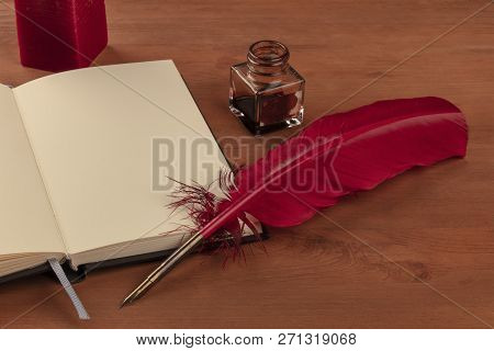 Poetry. A Photo Of A Red Quill With And Ink Well, A Candle, And An Open Notebook On A Wooden Desk Wi