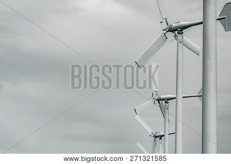 Horizontal Axis Wind Turbine With Grey Sky And Clouds. Wind Energy In Eco Wind Farm. Green Energy Co