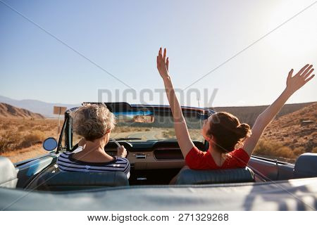 Mum driving car, daughter with hands in the air, back view
