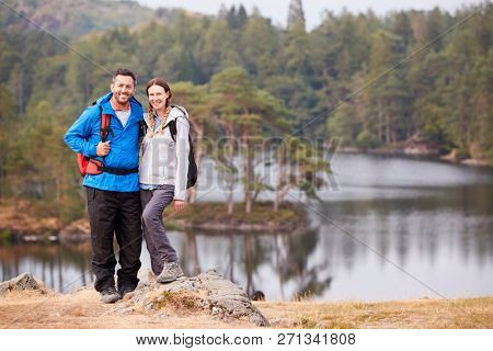 Young adult couple standing on a rock beside a lake in countryside, smiling to camera, full length