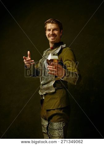 Medieval Smiling Happy Knight With Beer On Dark Studio Background. Portrait In Low Key Of Brutal Man