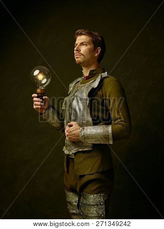Medieval Knight With Lamp On Dark Studio Background. Portrait In Low Key Of Brutal Man In Tradishion