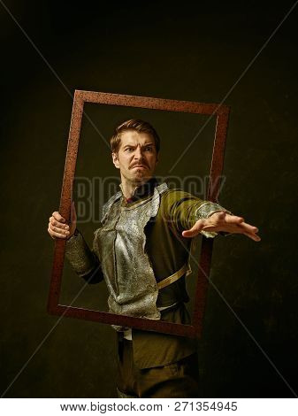 Medieval Angry Knight On Dark Studio Background. Portrait In Low Key Of Brutal Man In Tradishional R