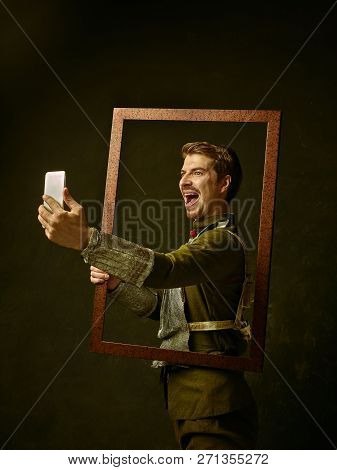 Medieval Knight With Mobile Phone On Dark Studio Background. Portrait In Low Key Of Brutal Man In Tr