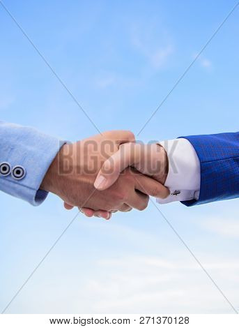 Partnership And Support. Successful Deal Handshake Blue Sky Background. Shaking Hands At Meeting. Fr