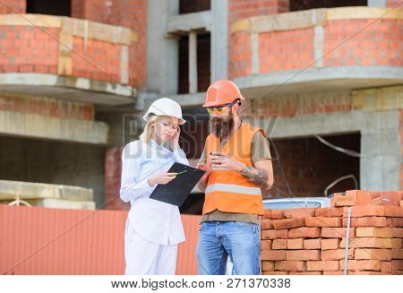 Discussing Plan. Woman Engineer And Builder Communicate At Construction Site. Construction Team Comm
