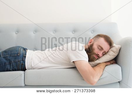 Handsome Bearded Man Lying And Sleeping On Stomach On Sofa. Young Guy Dozing. Rest Concept.