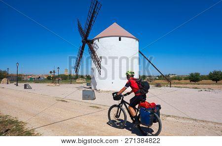 Biker pilgrim by Camino de Santiago in bicycle at windmill of Castile La Mancha
