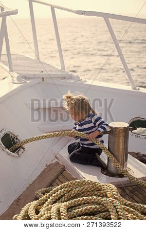 Yachting And Sailing Concept. Baby Care And Childhood. Little Child Sitting And Berthing Rope On Whi