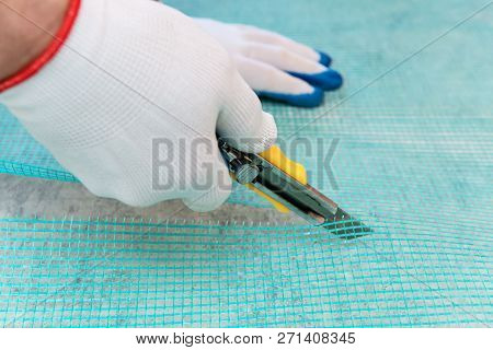 A Worker Is Cutting Off A Piece Of Fiberglass Mesh With A Knife.
