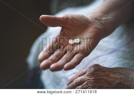 Pensioner Takes Medicine. An Elderly Woman Takes A Dose Of Medication. Medication In The Palm Of An