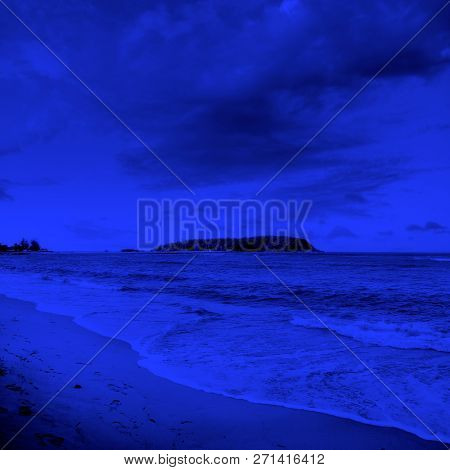seascape image of beach with island view over sunny cloudy sky