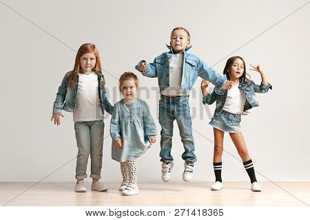The Portrait Of Cute Little Kids Boy And Girls In Stylish Jeans Clothes Looking At Camera Against Wh