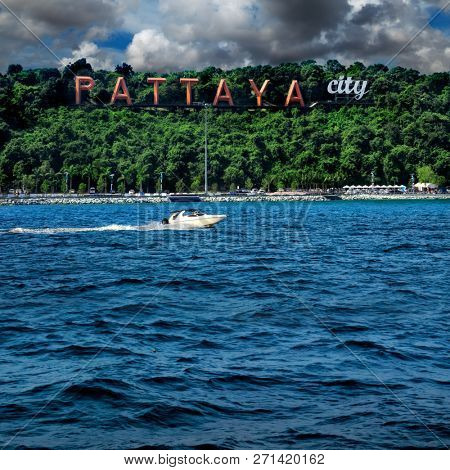 Pattaya city sign on green hill with blue sea water over cloudy sky in downtown Pattaya, Thailand