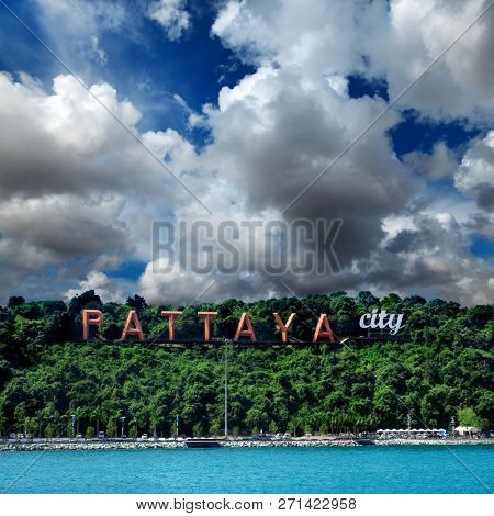 Pattaya sign on green hill over cloudy sky in Pattaya, Thailand