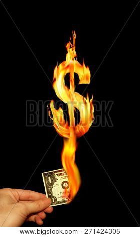 Conceptual image of hand holding burning one dollar bill and fire flamesof dollar sign in black background