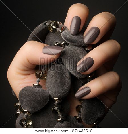 Female Hand With Shiny Dark Gray Nails Is Holding A Gray Jewelry On Dark Gray Background.