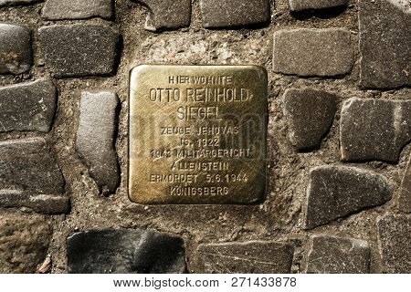 BERLIN, GERMANY - MAY 24, 2018: A Stolperstein, a golden cube with the name and life dates of a victim of nazi extermination, in the pavement of a street in the Charlottenburg district of Berlin