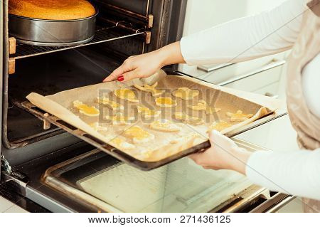 Woman Puts The Homemade Cookies On The Oven