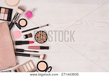 Makeup cosmetics and an open bag on white wooden background, top view with copy space
