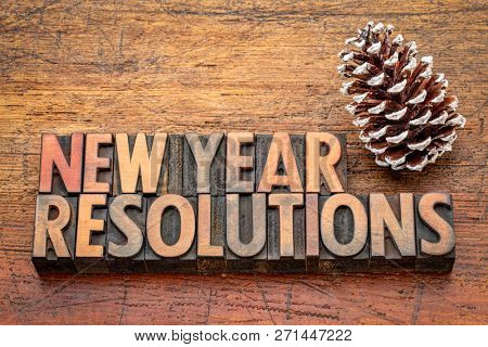New Year  resolutions word abstract in vintage letterpress wood type again rustic wooden board with a pine cone