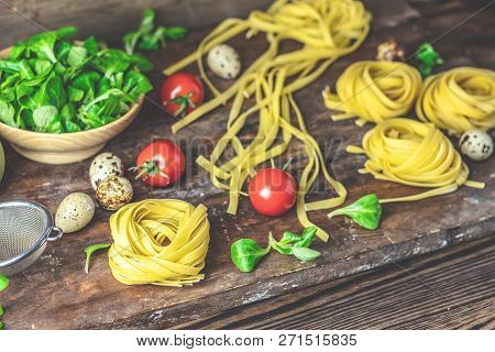 Raw Homemade Italian Typical Pasta Linguine Noodles, Quail Eggs, Green Lettuce, Tomatoes And Flour O